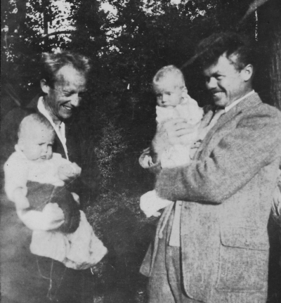 Two men in casual suit coats each holding their infant sons.