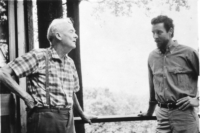two men stand on an outdoor deck - one older and one younger