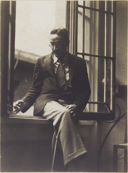 black and white photo of a man sitting cross-legged on a windowsill. He's wearing a jacket, tie and slacks, and is smoking a cigarette.