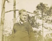 Sepia photograph of Wharton Esherick in front of trees wearing sweater and tie