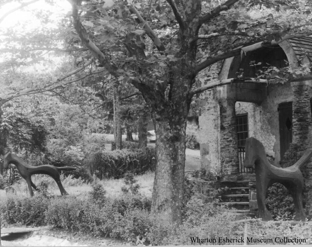 Black and white photo with large tree in the center and two large wood horse sculptures on either side, all in front of stone building with stone archway over front door.