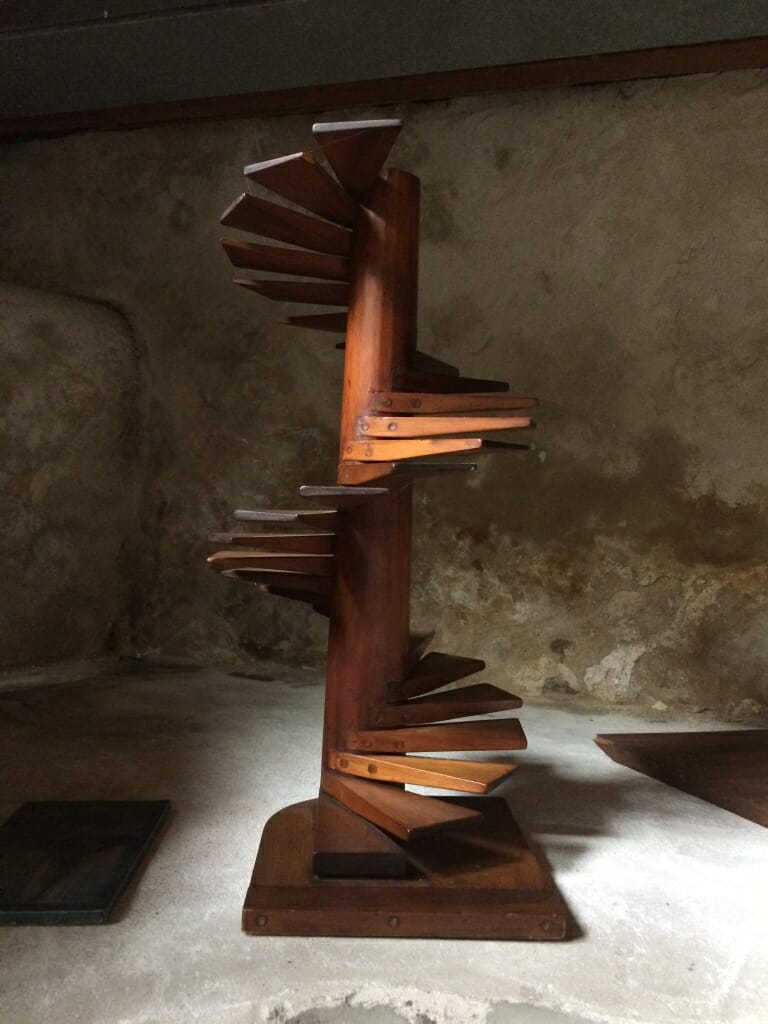 Wood model of spiral staircase with cantilevered steps spiraling up a central post.