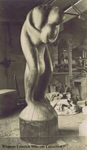black and white photo of large figurative wood sculpture depicting a passionate embrace of two people.