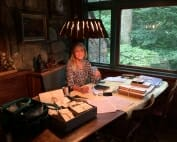 Young woman sits at table surrounded by woodcut blocks and paperwork.