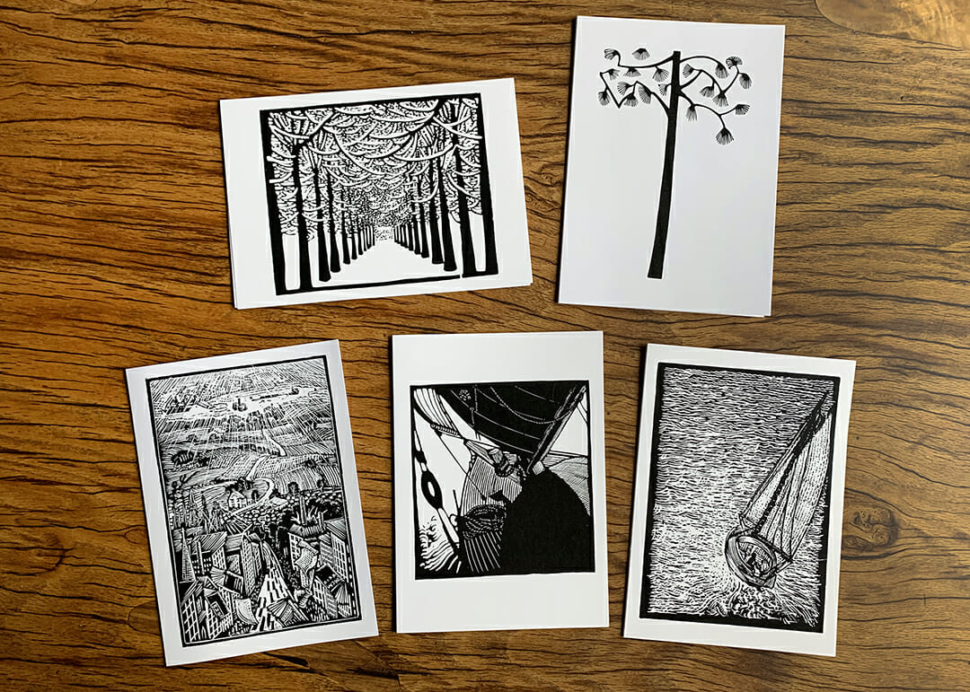 five black and white notecards lying on a wooden table