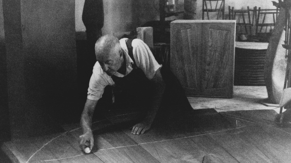 Black and white photo of older mandrawing a chalk line across wood boards in a workshop.