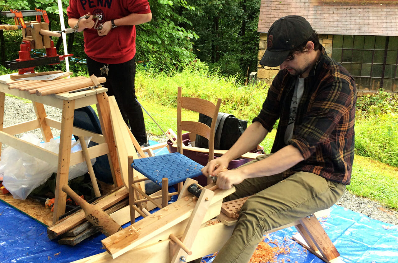 Young man using drawknife to shape a chair leg. Chair in background.
