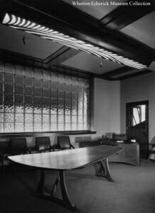 black and white photo of large organically curved table with chair against wall of room and long ceiling light cover above which mimics woodcut gauge lines.