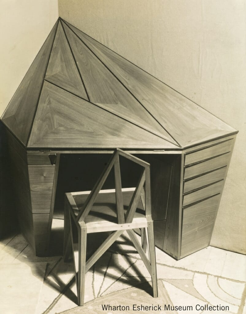 black and white photo of prismatic or faceted diamond shaped corned desk with chair