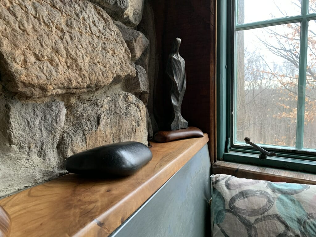 smooth black stone sits on the shelf behind bench