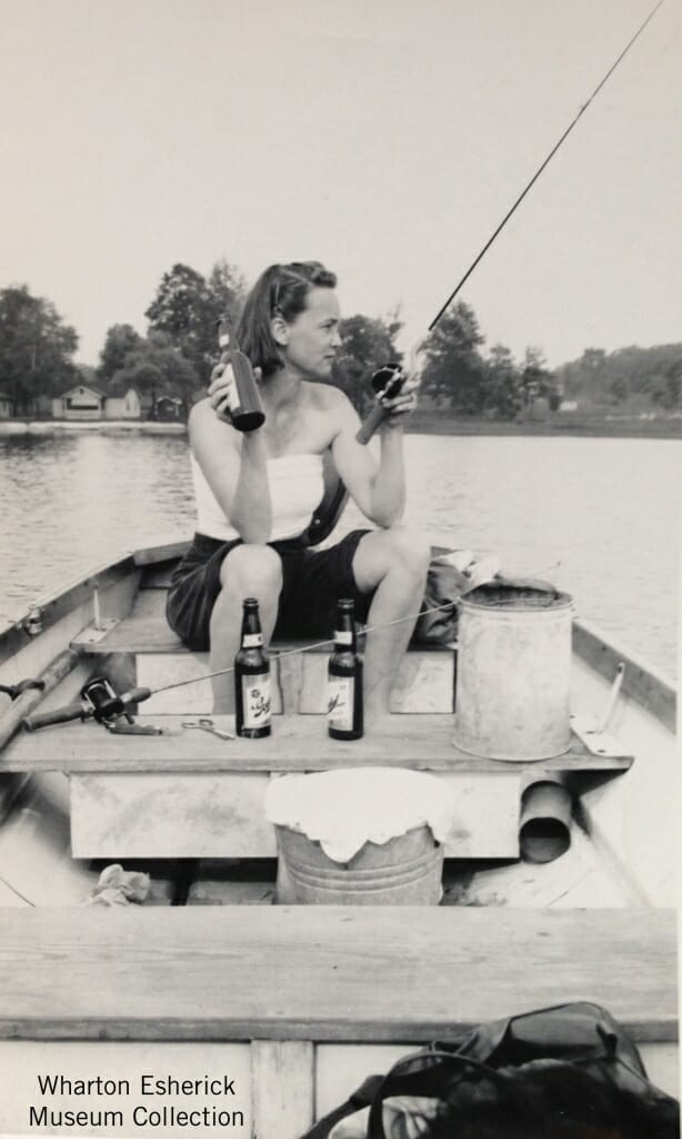 woman seated ina boat, drink beer and fishing on a lake