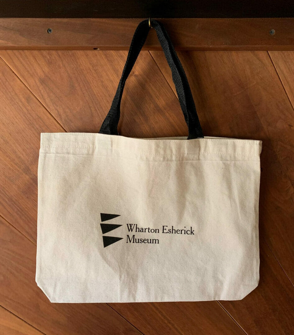 natural canvas tote bag with black museum logo and handles
