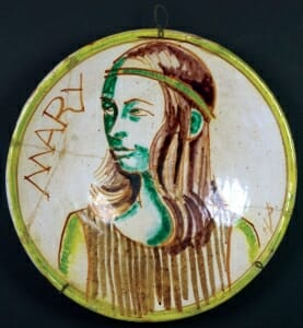 ceramic plate with grena nd brown painting of young girl with headband in three-quarters view.