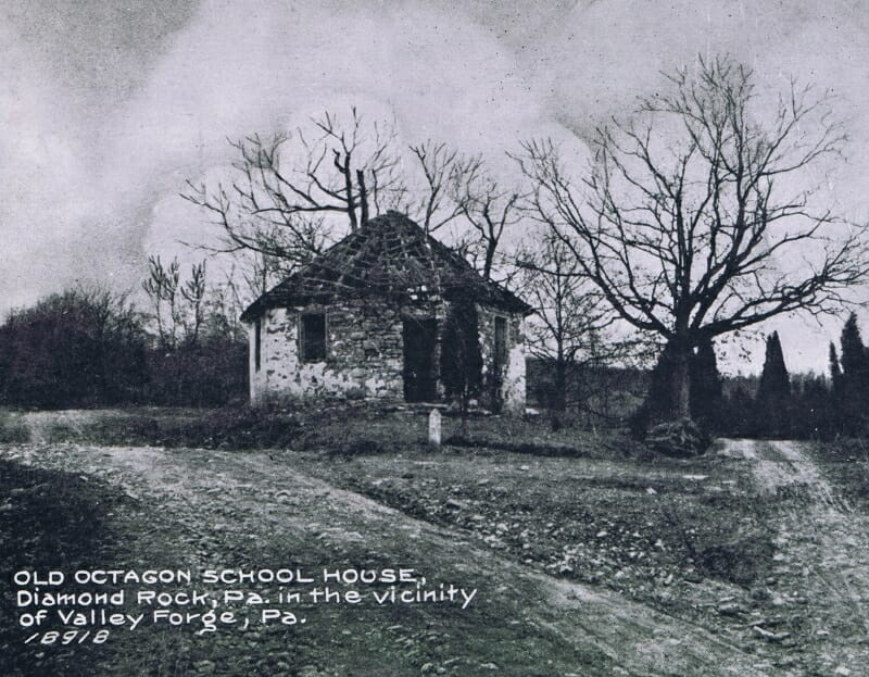 black and white historic photo showing schoolhouse in disrepair with roof shingles missing and walls crumbling.