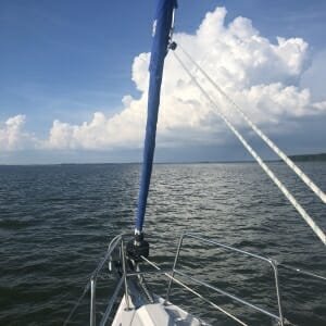 view from bow of boat, all water with a few white clouds