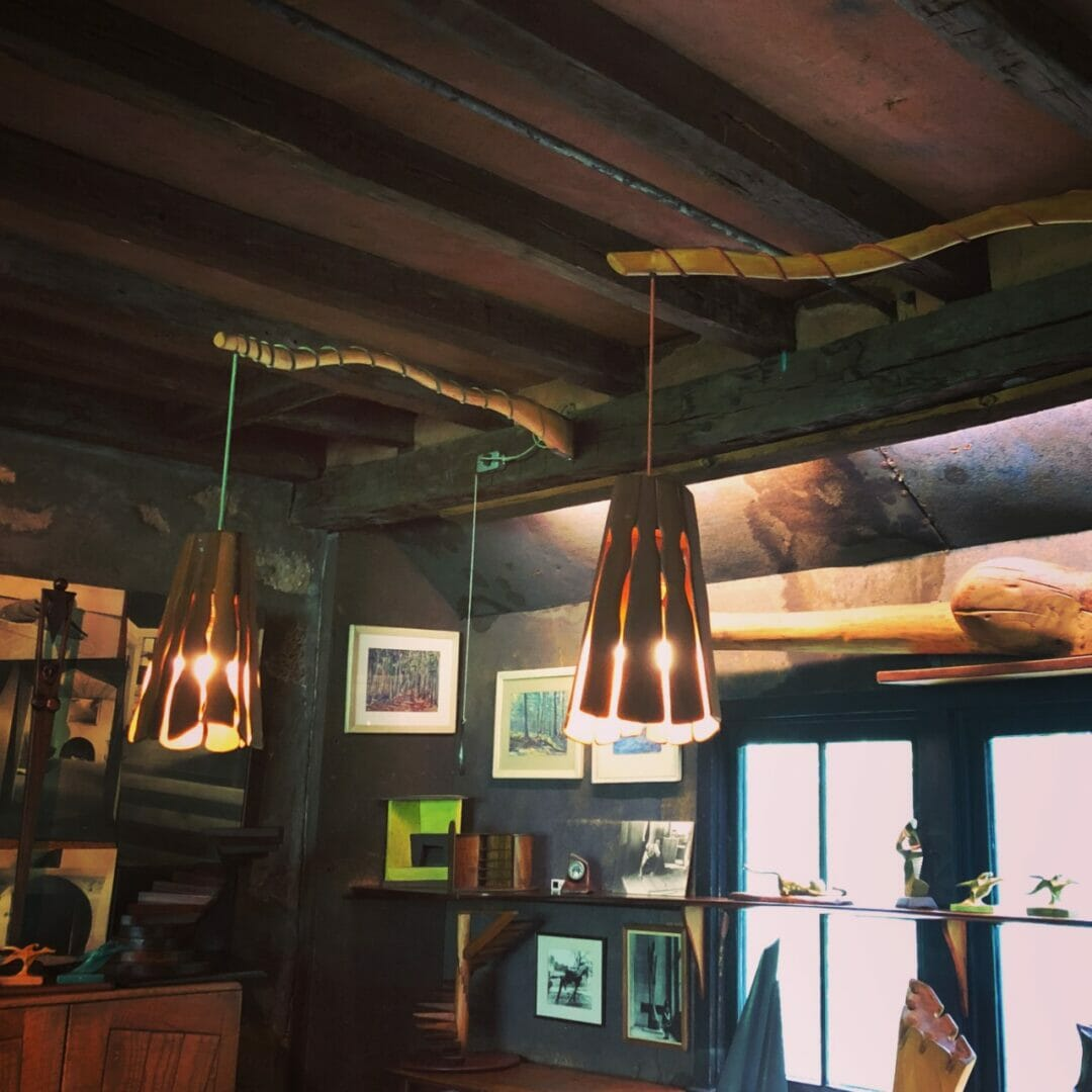 two wood lampshades dangle from cords wrapped around wood armatures