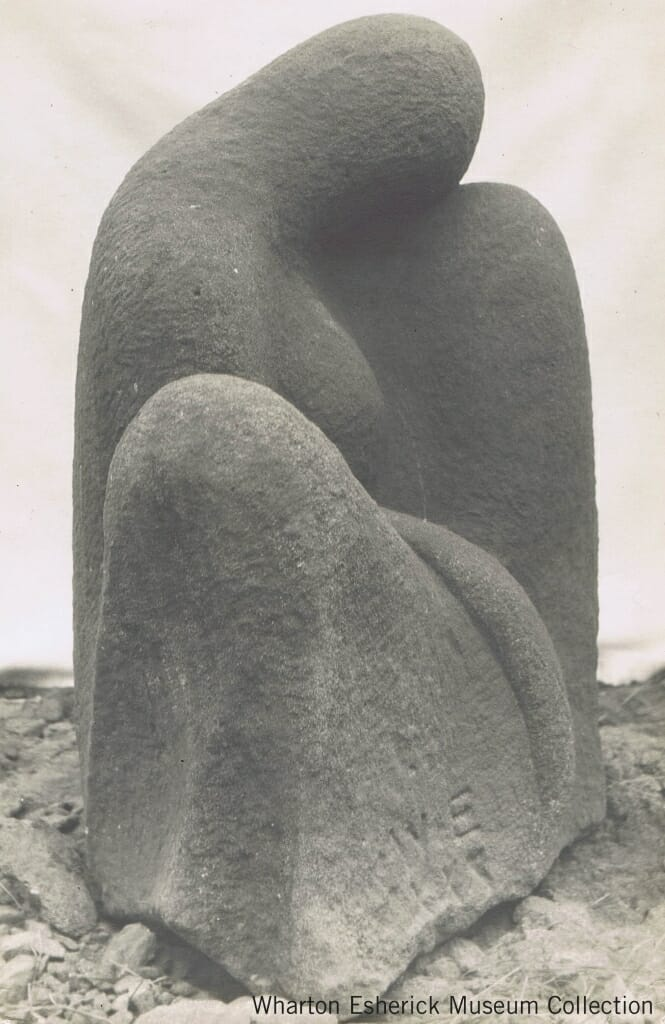 sandstone carving of seated figure simplified to three mounded forms