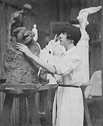 woman in white studio apron works on clay figurative sculpture