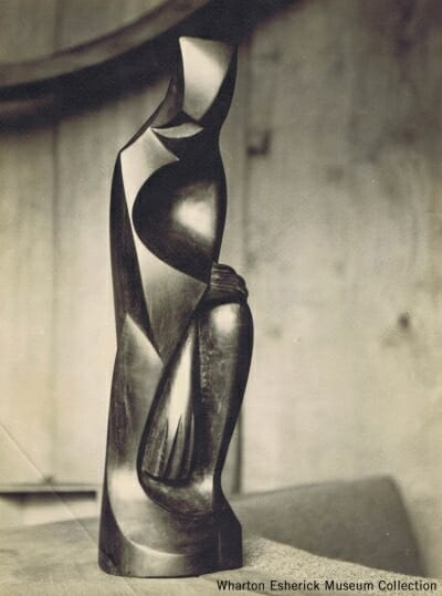 wood carved sculpture of crouching figure