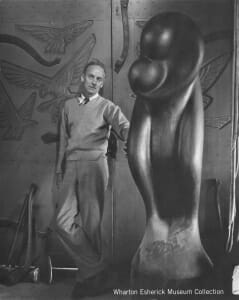 man (Wharton) in sweater and slacks leans against carved wood loading doors with large wood sculpture by his side. sculpture is rounded abstration of two people in an embrace.