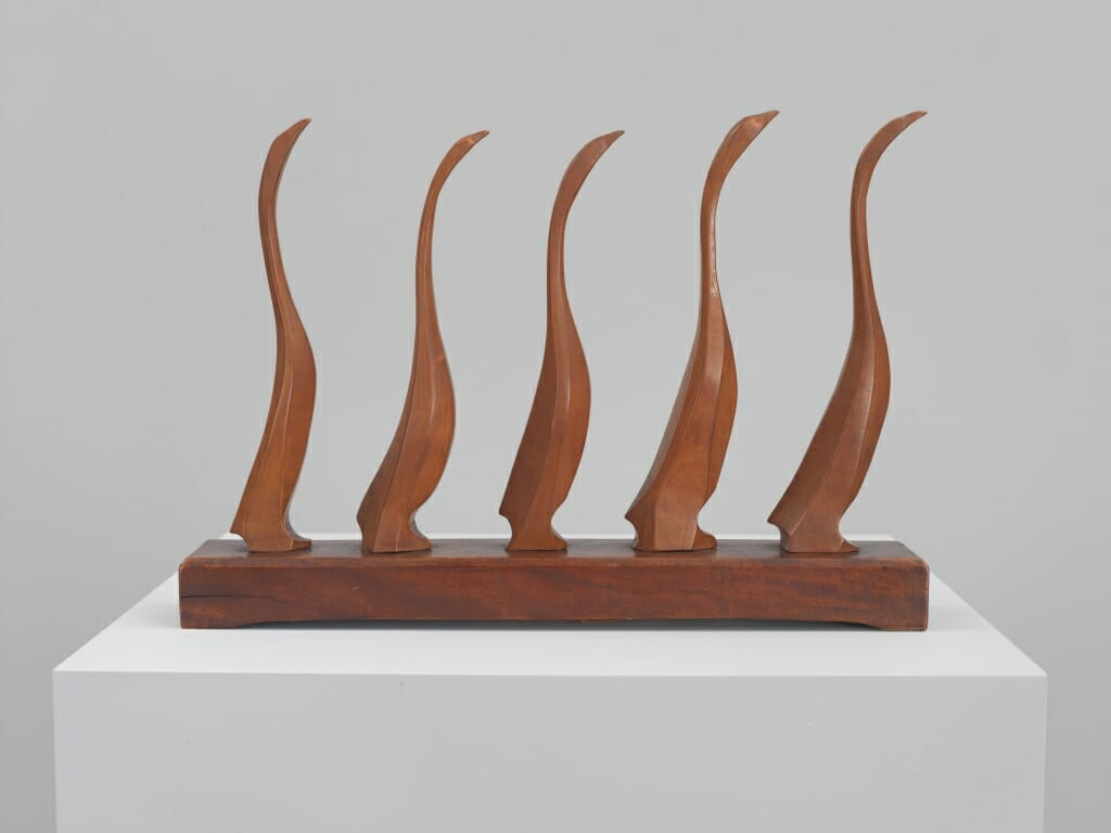 wood sculpture of five goslings in a line