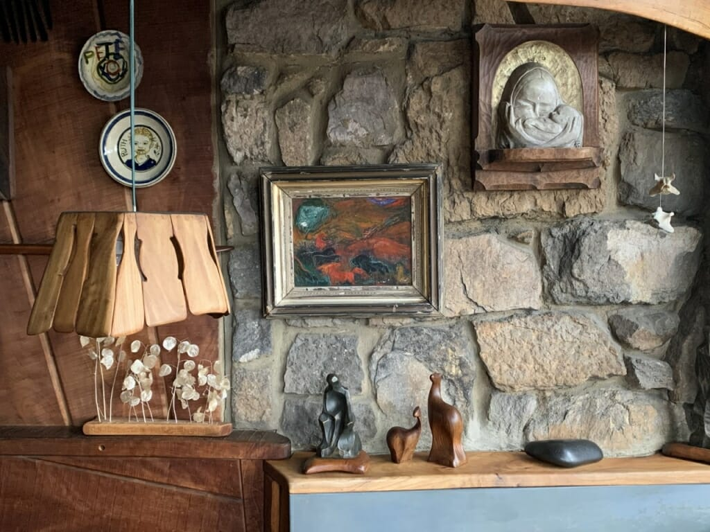 wall, part wood, part stone with ceramic plates, soapstone carving and painting on display