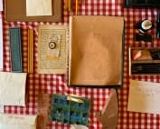 view from above of papers, pencils, ink bottles, envelopes spread out over checkered tablecloth