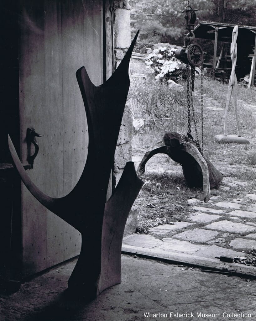 abstract wood sculpture on packed earth floor in front of open loading doors with more wood sculpture in the yard