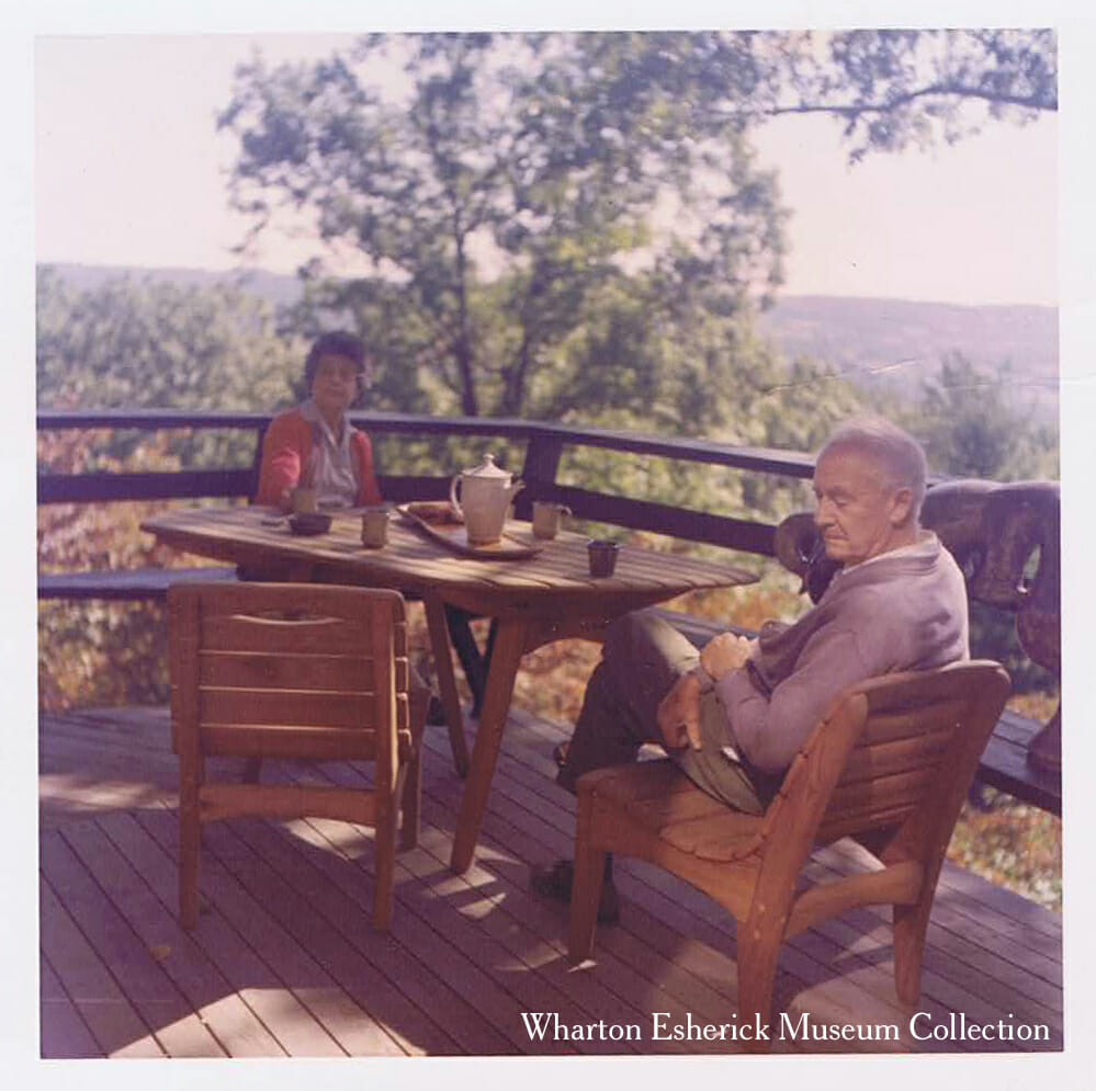 Elderly man and woman sitting on wood deck overlooking woods