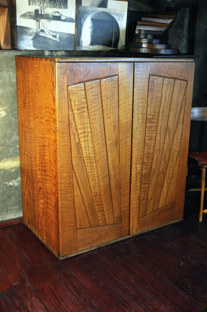 wood cabinet with doors with boards laid out in a fanning design on the front