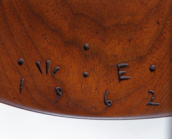 detail of wood surface with initials W. E. and 1962 carves into the surface