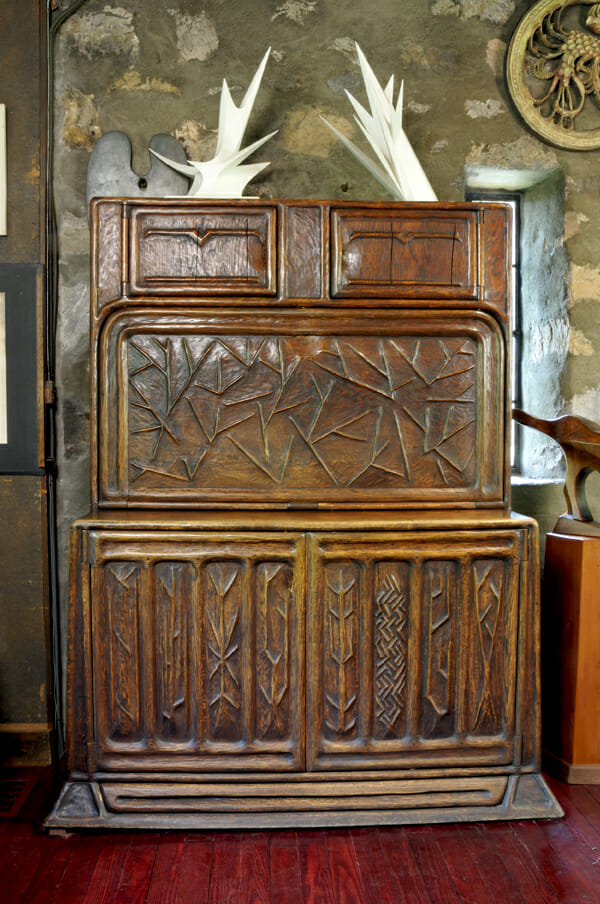 large drop leaf desk with carved surface with designs of trees and bare branches