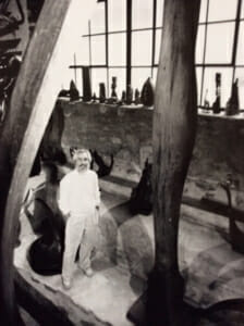 man standing among many tall wood sculptures, windosill of small wood sculptures behind him