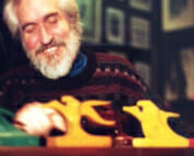 Smiling man with beard looking at small wooden carved sculpture