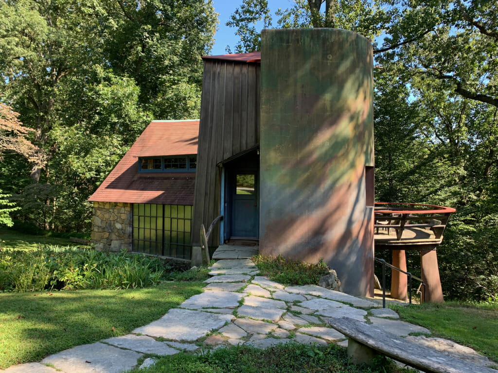 view of studio building with stone section on left and stucco silo on right dappled in shadows from the trees