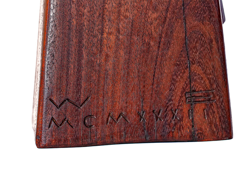 detail of wood base with carved initials and roman numeral date