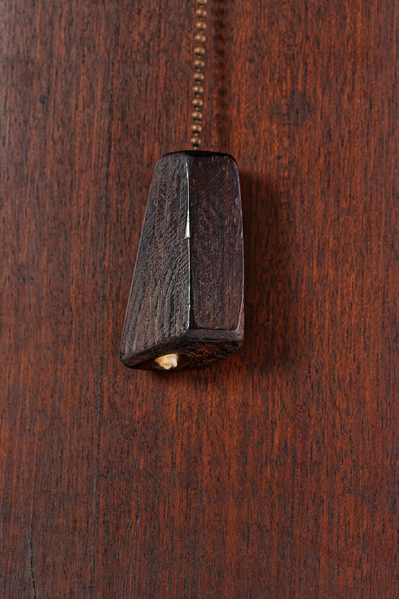 detail of pull chain with faceted wood pull at end of metal chain