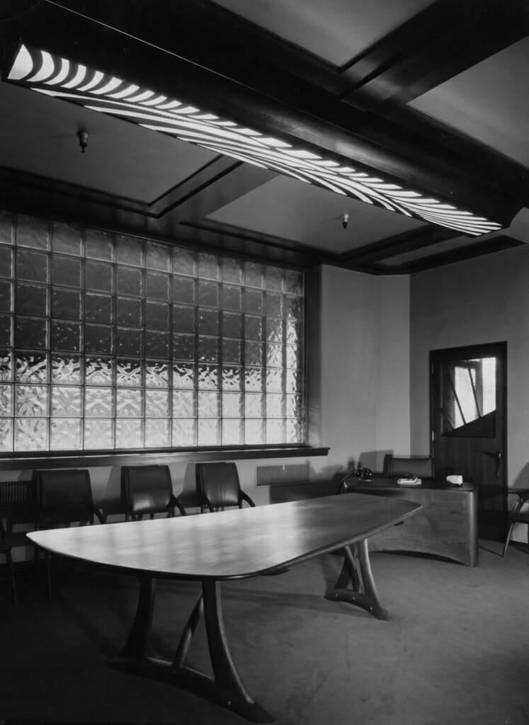 organic curving boardroom table with glassblock window behind and ceiling light with curving patterned grille over long rectangular light