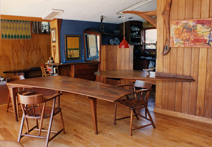 dining area of home with wood walls with blue accents. Rectangular but curving dining room table surround by captain's chairs in the center of the space with cantilevered breakfast counter and entrance to kitchen in the background