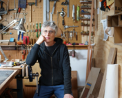 Woman in workshop in front of wall of woodworking tools