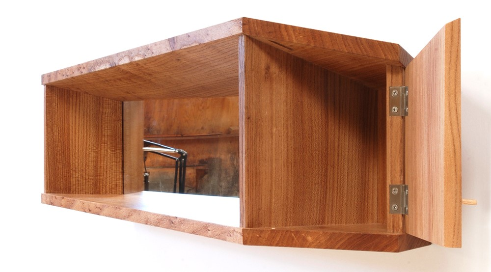 rectangular wood wall shelf and cabinet with prismatic angles and mirror behind shelf