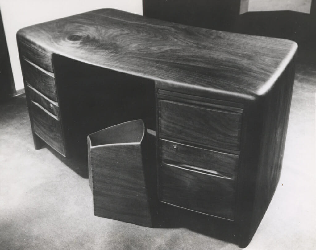slightly curving rectangular desk with faceted geometric wastebasket, all made of wood