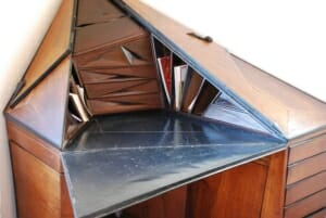 triangular desktop of a wooden prismatic shaped or diamond shapes desk with drawers and organizational cubbies.