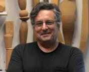 man in black t-shirt with arms folded across chest is smiling. Turned wooden forms hang on a wall behind him.