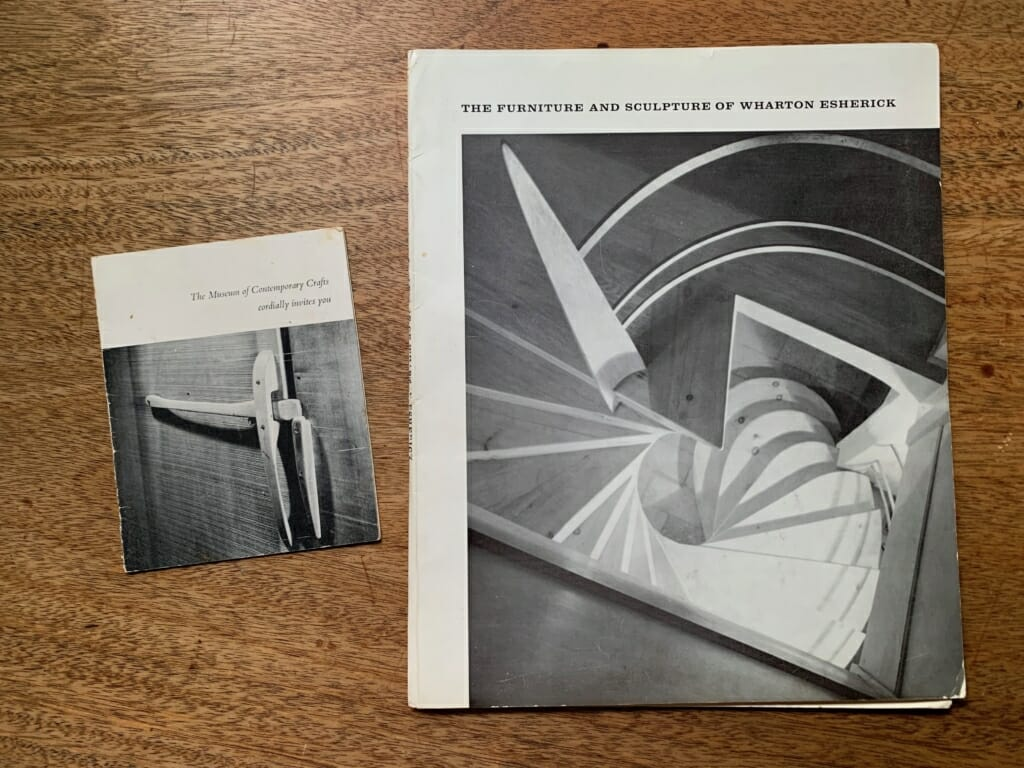 A black and white exhibition catalog and a smaller notecard-sized invitation lay on a solid wood desktop. The catalog features the title 'The Furniture and Sculpture of Wharton Esherick' and a view looking down at a spiraling staircase made for the Curtis Bok house. The invitation includes a black and white photo of a slender wooden door latch with the words 'The Museum of Contemporary Crafts cordially invites you' written above.