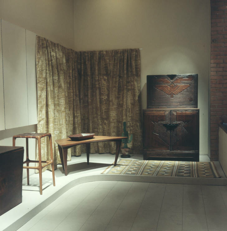 view of gallery showing several pieces of wood furniture wrapped around two wall of the room. From left to right stand a four legged stool with a woven leather seat, an asymmetrical coffee table with a darker wood bowl on top and a carved wood cabinet and desk unit. These is also a greenish-tan curtain hanging in the corner of the room, and a woven rug on the floor in front of the desk unit.