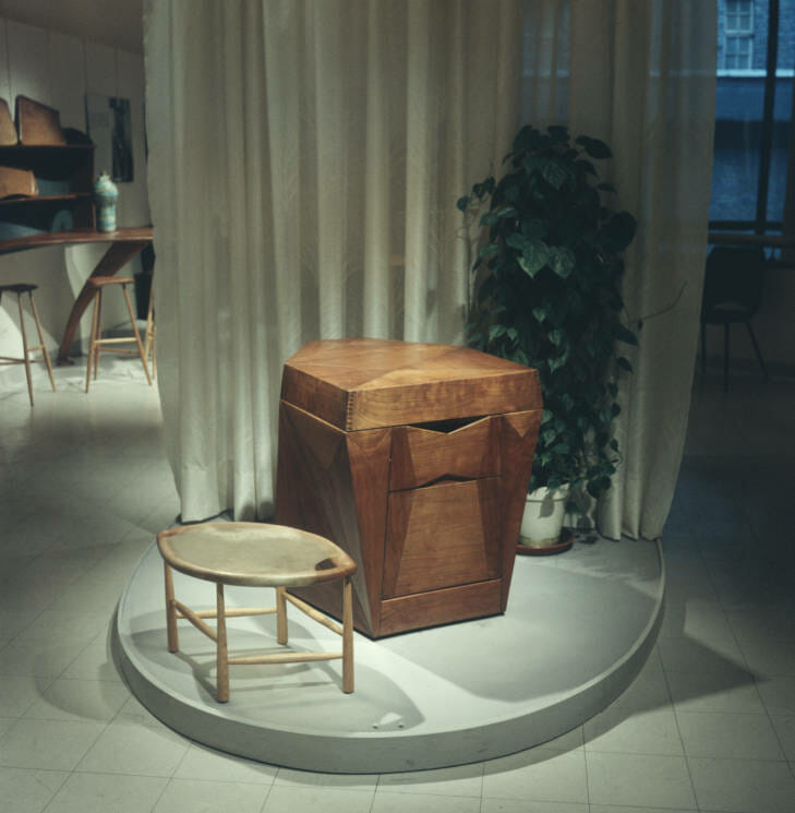 ovoid plinth in the center of a gallery with a short wood stool with an almond shaped seat made of rawhide next to a wood phonograph cabinet. The cabinet is a boxy form, but has faceted asymmetrical planes. there is a soft white curtain behind them and a houseplant. far behind the curtain we can see a couple stools and other furniture.