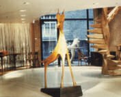 Wood sculpture of a deer stands in the foreground of a gallery space. A Wooden spiral staircase stands to the right, in front of a brick wall, and the back wall of the room is all glass. Through the window is another wood animal sculpture, this one a horse. Inside to the left is a captains chair and a table with a carved bowl on top.