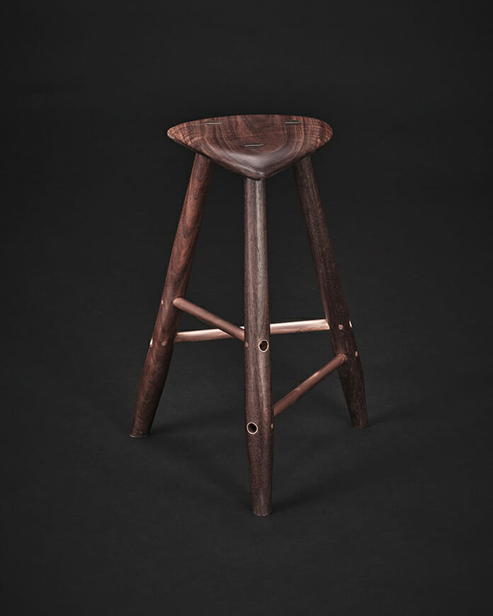 three legged wood stool with copper struts photographed against a black background