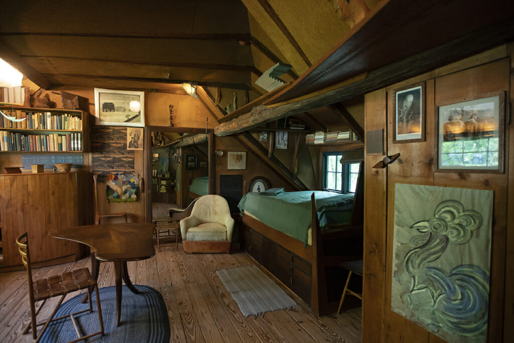 a view of Esherick's bedroom shows bad to the right with light from the window above it. Pictures and drawings hang on the wall and a large mirror hangs on the far side of the room. A leather chair sits near the foot of the bed and a three-legged table with a grand piano-ish shaped top and a chair sit in the center of the room on a blue oval braided rug. Book shelves can be seen above the bed and above a dresser on the far side of the room.